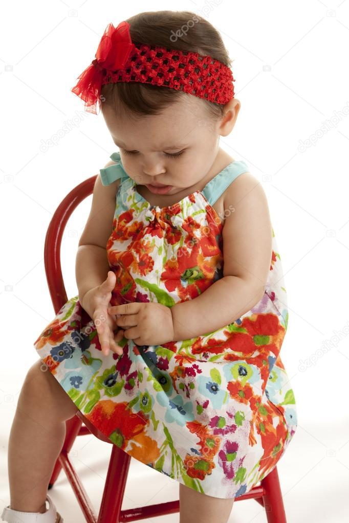 cc7013334 niña con un vestido muy floral sentado en la silla pequeña — Foto de ...