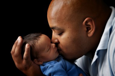 African american father cuddling and kissing his newborn son