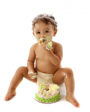 Cute toddler girl eating her first birthday cake
