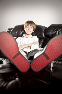 Preteen boy with big feet relaxing