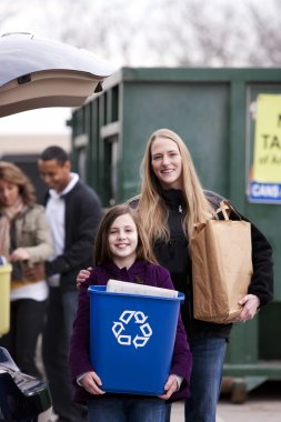 Mother and daughter recycle trash at recycling сenter