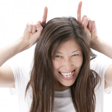 Asian woman with mschievous expression and devil horns