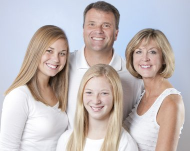 Headshot of smiling family of four with mother, father and two daughters