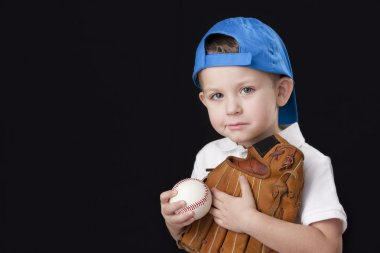 Portrait of little boy wearing baseball cap and holding baseball mitt