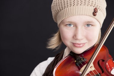 Close up of caucasian little girl playing a violin