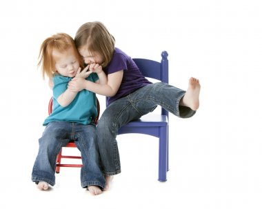 Two sisters sitting together and playfully wrestling