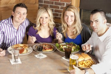 Caucasian adult couples eating together at a restaurant.