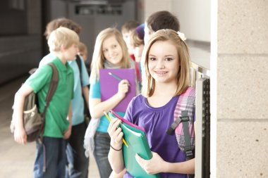School Education. Group of middle school age students talking at their lockers during a break from class