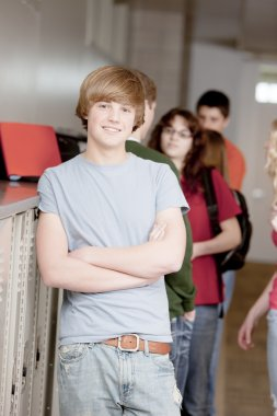 A three quarter length image of a teenage high school student standing at his locker during a break between classes. stock vector