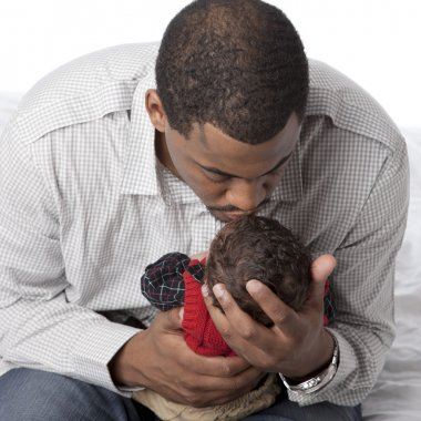African american father kissing his newborn baby son