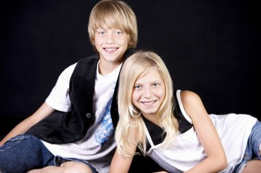 A three quarter length image of caucasian fraternal twins, a brother and sister in a studio shot with a black background, They have blond hair and blue eyes. stock vector