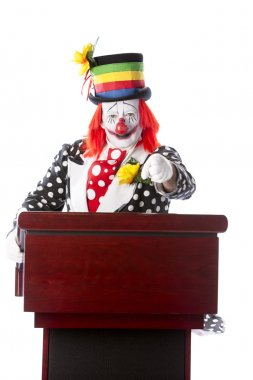 A three quarter length image of a smiling adult clown standing at a podium giving a speech and pointing at the camera. stock vector