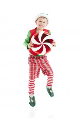 One of Santas сhristmas elves dances with a large candy peppermint.