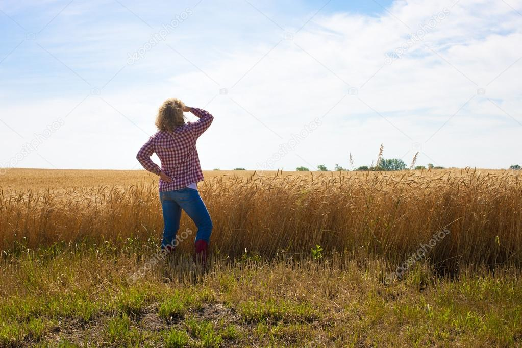 A hardworking female farmer looks out