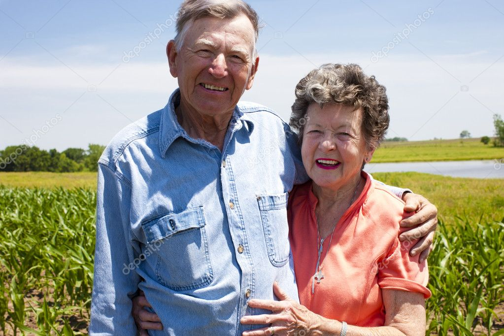 A proud hardworking midwestern grandmother and grandfather, farmers, stand proudly together in love