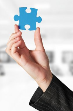 Business concept: Hand holding the missing jigsaw puzzle
