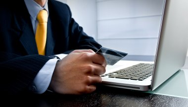 e-commerce concept: business man paying online with his credit c