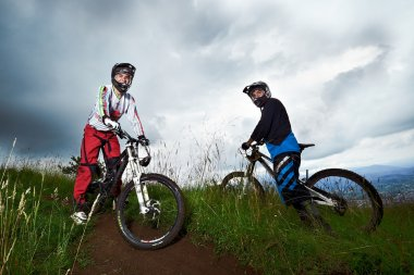Two young man riding a mountain bike downhill style