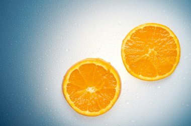 Two oranges over a white and blue wet background with water drops stock vector