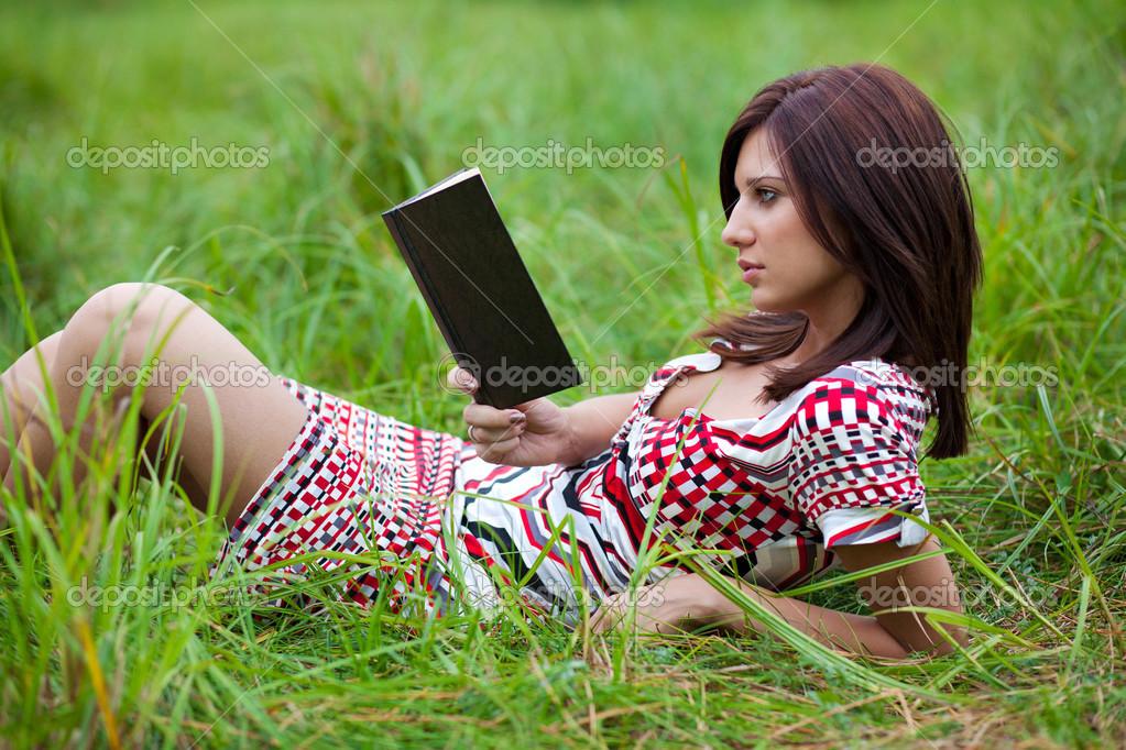 Chica Morena Leyendo Libro Tumbado En La Hierba