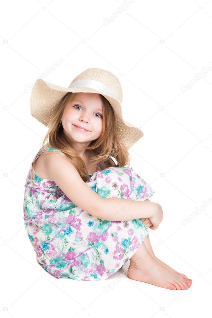Niña rubia vestida con sombrero blanco y vestido sentado en la fl — Foto de  Stock 64a0c7cc1b5