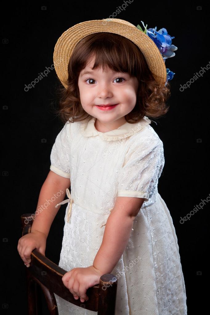 Linda niña de vestido blanco y sombrero con flores de color azul — Foto de  Stock 2222d7521d1
