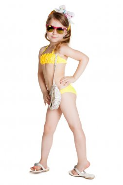 Little blonde girl wearing swimsuit, sun glasses and bag