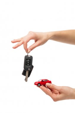 Two hand holding red colored car with automatic key