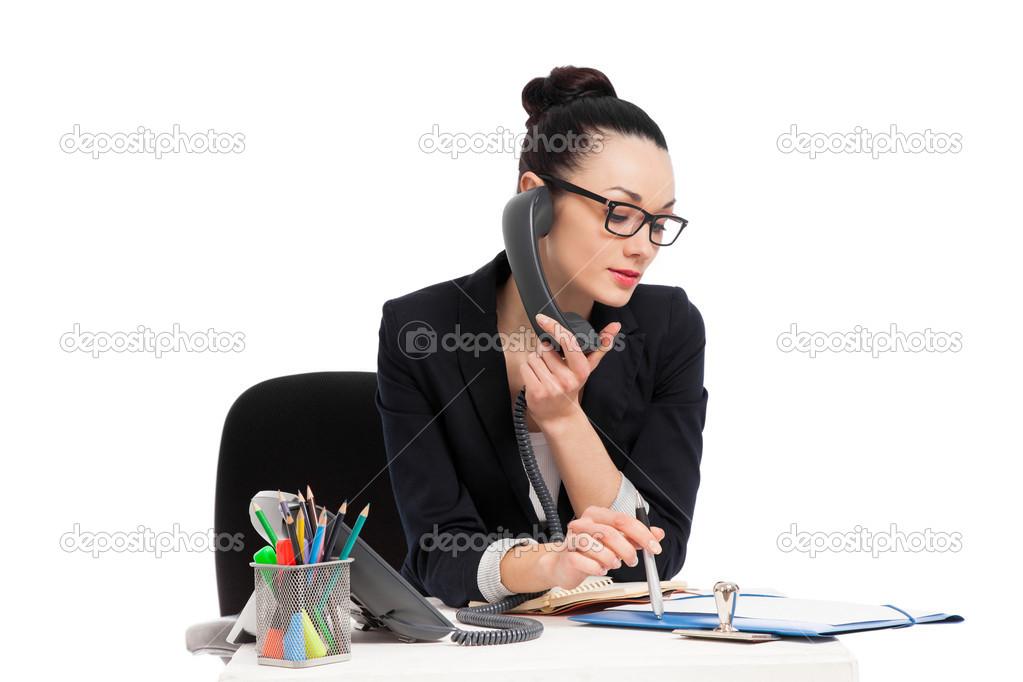 Secretaria morena hablando por tel fono sentado en mesa for Ministerio de seguridad telefonos internos