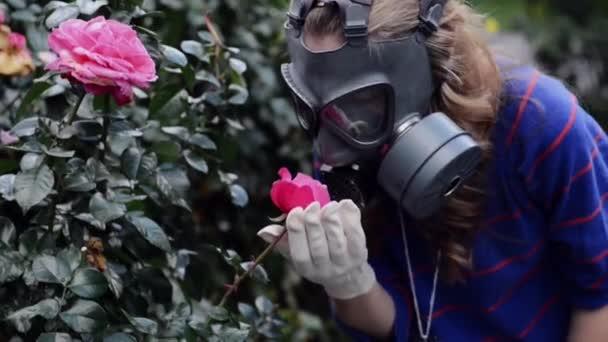 Girl in gas masks smells roses
