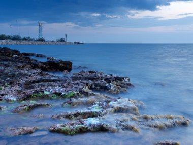 Seashore during sundown. Stone and lighthouse