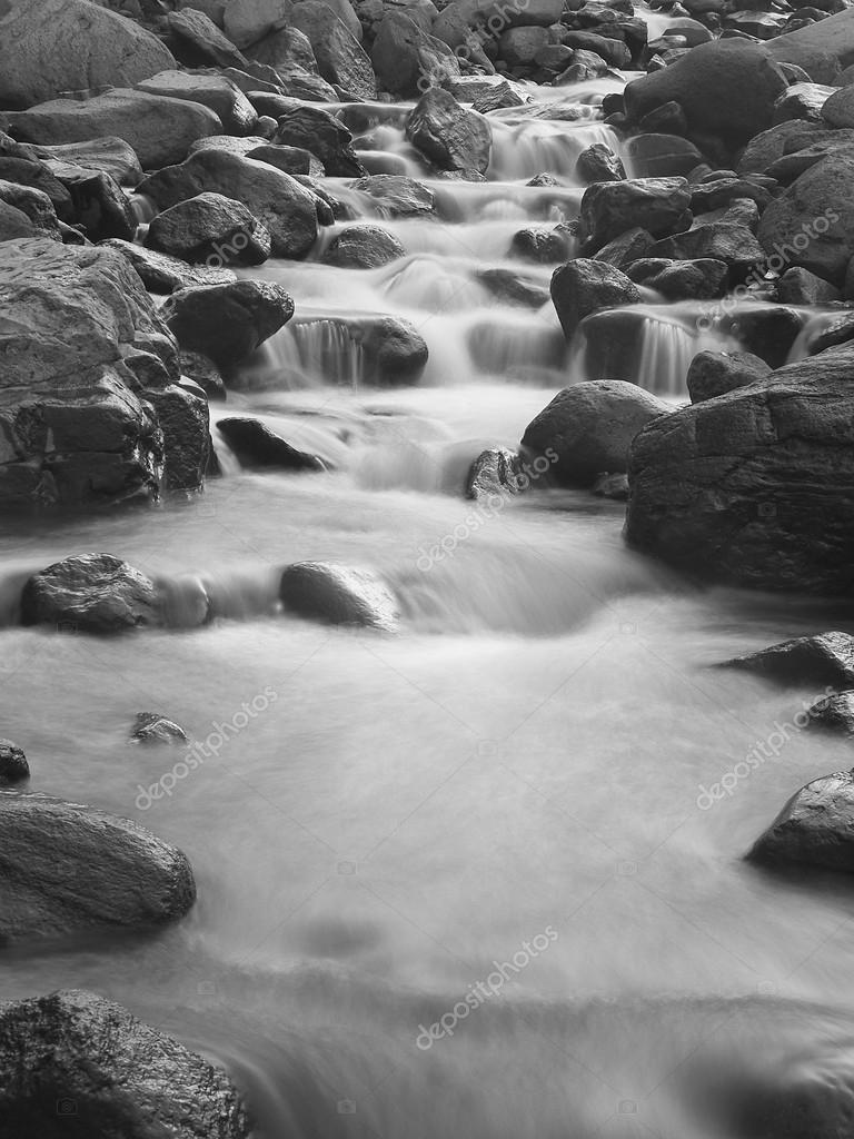 Fast river and stone. Monochrome composition