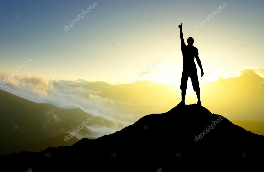 Male silhouette showing thumb up on mountain top
