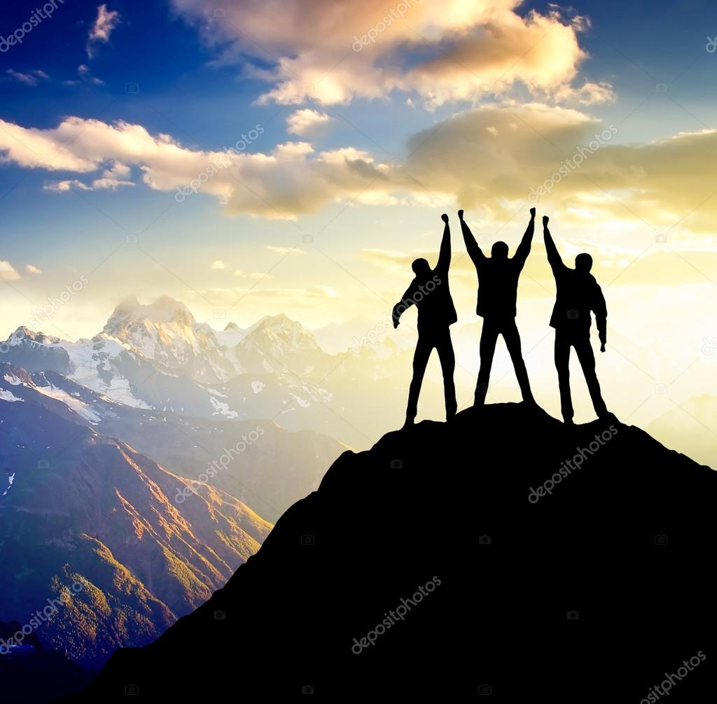 Silhouette of the team on the peak of mountain