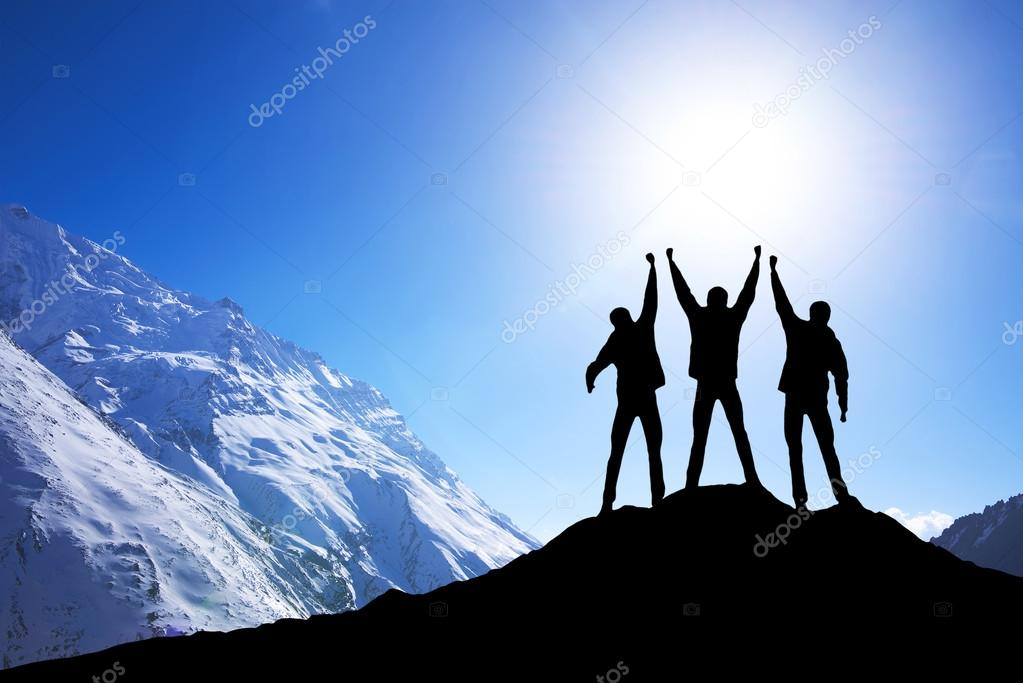 Silhouette of team on mountain peak