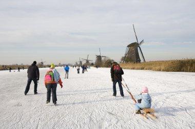 Skating scene with Dutch historic windmills at Kinderdijk