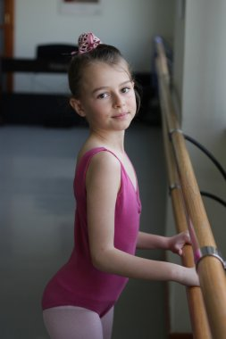 Ballet girl standing next to the barre