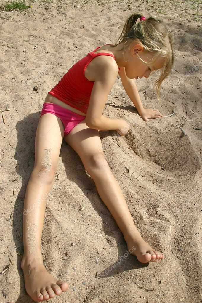 Girl drawing in the sand
