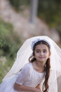 Young girl outside in a holy communion dress