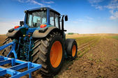 Velký traktor v poli - v pěkné modré slunečný den
