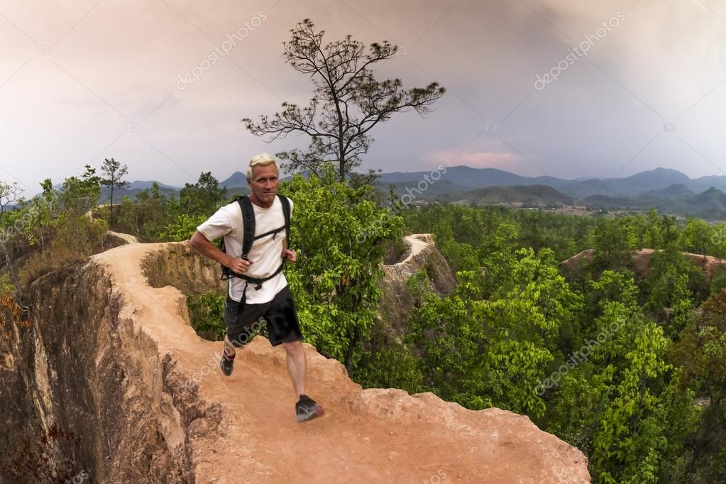 Man hiking and running in mountains wearing white shirt and backpack