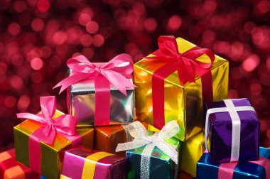 Pile of small gifts on red blurry lights background.