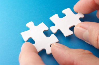 A person connecting puzzle pieces.