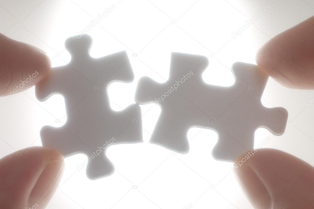 a person connecting puzzle pieces against the light stock photo