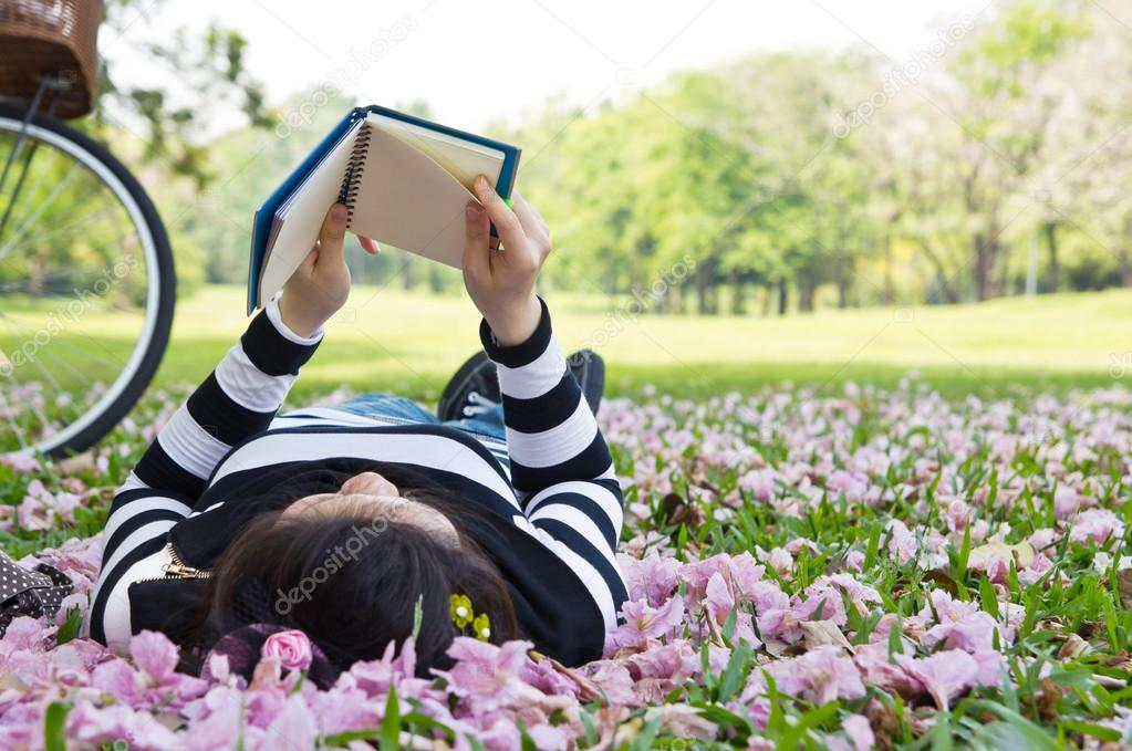 Asian woman reading booklet on the grass