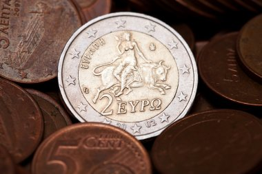 Greek two euros coin among coins of five cents