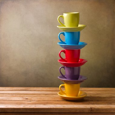 Colorful coffee cups on wooden table over grunge background stock vector