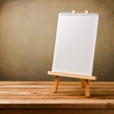 Blank note book on easel on wooden table