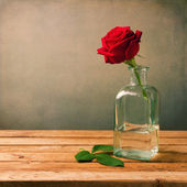 Photo Red rose on wooden table