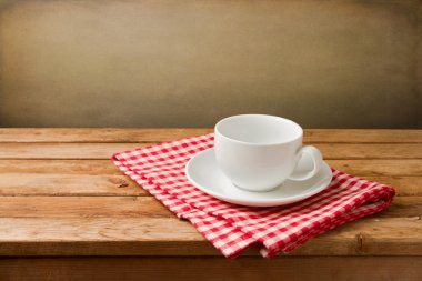 Empty coffee cup on tablecloth on wooden table